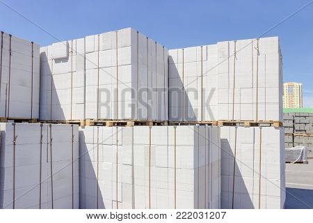 Wall panels made of the autoclaved aerated concrete on wooden pallets put one on the other on an outdoor warehouse