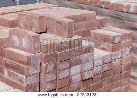 Brown decorative bricks stacked on a pallet on a blurred background of other building material on an outdoor warehouse