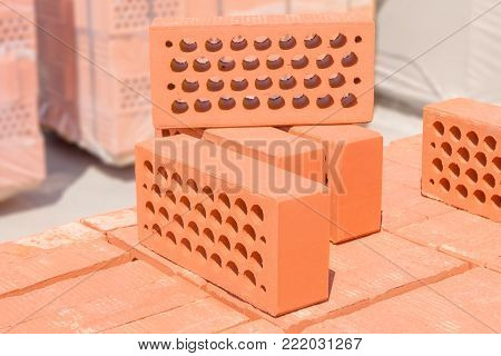 Several red perforated bricks with round holes put on the pallet of the same brick on a blurred background of other building material on an outdoor warehouse