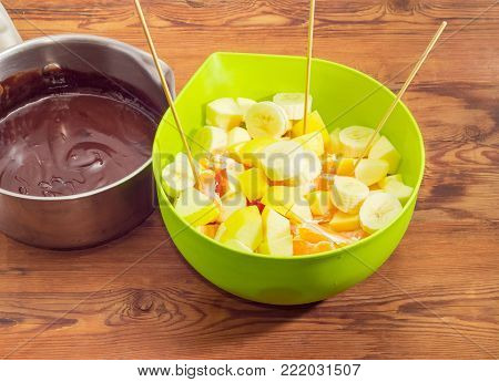 Chocolate fondue - pot with melted chocolate mixture and green plastic container with pieces of different fruits on an old rustic wooden table