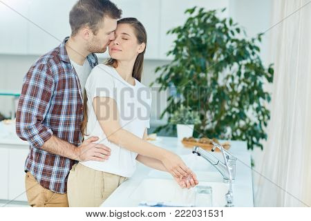 Young amorous couple standing by sink in the kitchen, man embracing his wife while she washing her hands