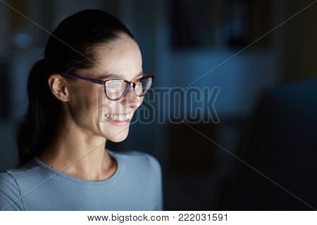 Happy young employee in eyeglasses staying in office at night and watching webcast or talking through video-chat