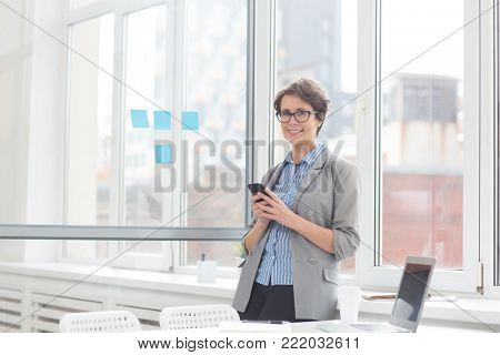 Contemporary accountant in formalwear standing by office window and messaging