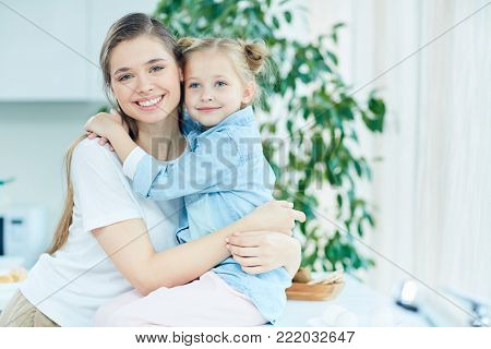 Cheerful and affectionate mother and daughter in embrace spending time at home