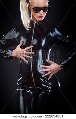 Portrait of blond woman in latex costume on black background