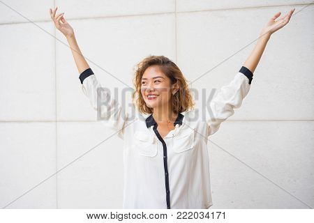 Portrait of happy young Asian woman raising hands in success. Manager getting prize. Business woman closing good deal. Business success and good news concept