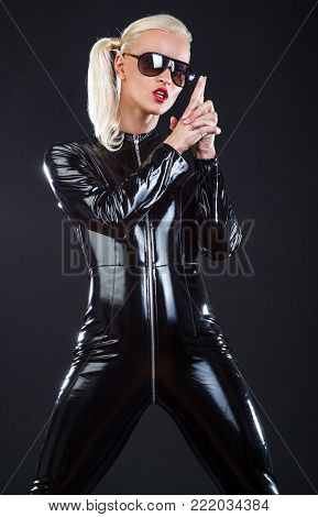 Blond woman in sunglasses and latex costume posing in studio