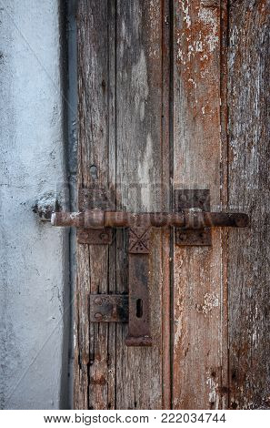 Demaged old wooden door with peeling paint and iron lock