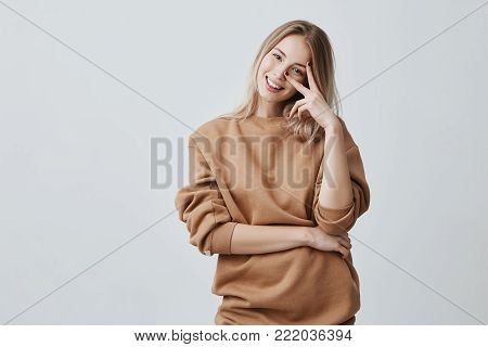 Horizontal portrait of Caucasian good-looking attractive young female model with long blonde hair dressed in casual clothes posing indoors, smiling broadly during interesting conversation. Young woman expressing positive emotions
