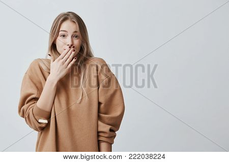 Shy young woman. Close-up portrait girl with blonde hair looking ashamed or shy, being in full disbelief, shocked by news, hiding face behind hand, isolated against gray background.