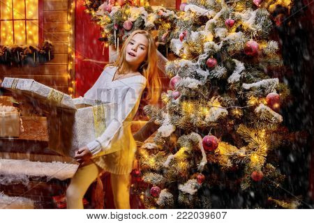 Pretty child girl is standing near her house decorated for Christmas and opening a gift box and surprises. Time for miracles.