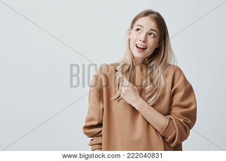 Pretty smiling joyfully female with fair hair, looking upwards, pointing index fingers, showing copy space for advertising content. Good-looking beautiful girl isolated against studio wall.