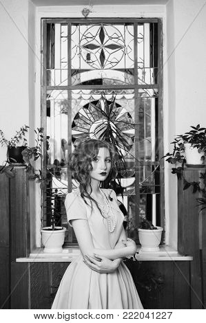 Black and white art monochrome photography. Black and white creative photography. Black and white conceptual image. Beautiful black and white background. Black and white portrait. A woman with curly hair in dress on background vintage window.