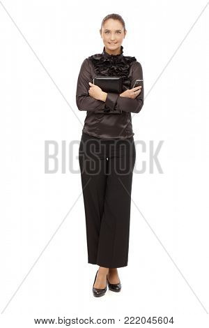 Smiling businesswoman in black holding personal organizer and phone, arms and legs crossed, cutout on white.