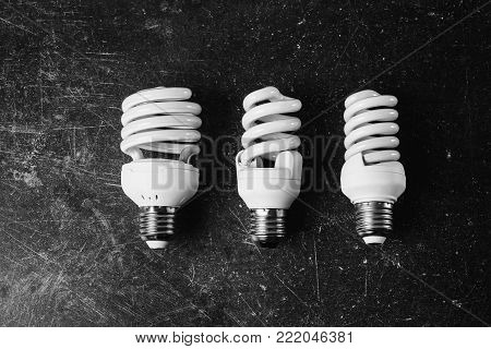 Fluorescent light bulb on a dark marble background. Black and white art monochrome photography. Black and white creative photography. Black and white conceptual image. Beautiful black and white background.