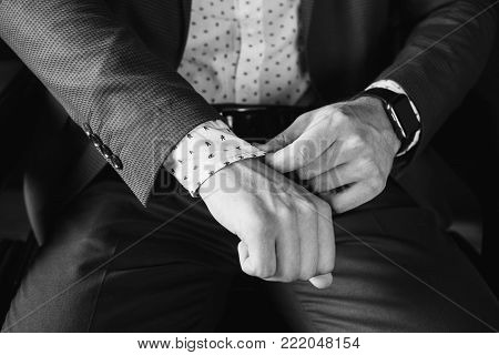 A successful young businessman in a business suit adjusts the sleeve. Black and white art monochrome photography. Black and white creative photography. Black and white conceptual image. Beautiful black and white background.