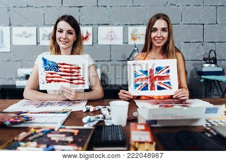 Two smiling female designers of prints showing their works, American and British flags drawn with watercolor technique, sitting at their work desk in creative office.