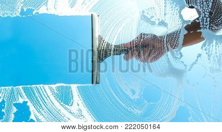 hand use puller to clean a glass window against blue sky, including copy space. ideal for websites and magazines layouts