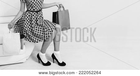 Girl in stylish dress and black shoes with shopping bags. Black and white art monochrome photography. Black and white creative photography. Black and white conceptual image. Beautiful black and white background.