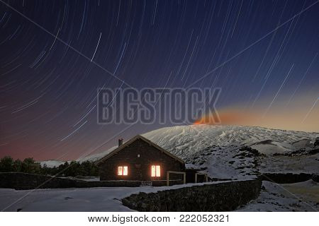 star trails on Galvarina Refuge with windows glowing under snowy Etna Volcano, Sicily