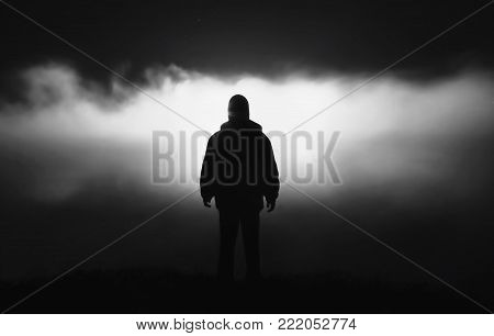 Silhouette of a man in the darkness. Night Photography. Black and white art monochrome photography. Black and white creative photography. Black and white conceptual image. Beautiful black and white background.