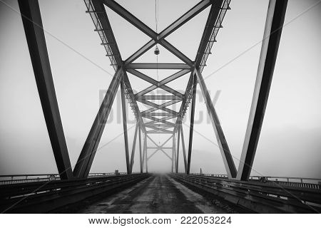 The bridge is illuminated by light from the rising sun. Black and white art monochrome photography. Black and white creative photography. Black and white conceptual image. Beautiful black and white background.