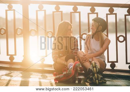 Two slim and sexy young women and roller skates. One female has an inline skates and the other has a quad skates. Girls ride in the rays of the sun.