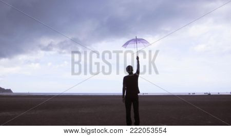 Blurred,A man carrying a pink parachute stands on a beach by the sea and the clouds are forming rain.