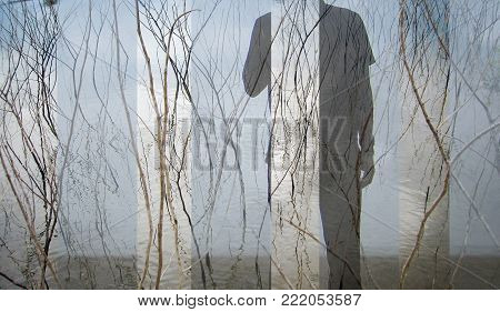 The man stands lonely with dried branches up from the water. The image overlays can be used as a background.