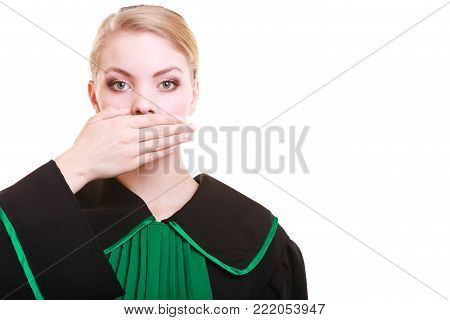 Law court or justice concept. Womn lawyer attorney wearing classic polish (Poland) black green gown covering mouth with hand. Confidential information.