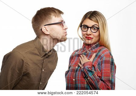 Shocked girl in styling checkered shirt and oval spectacles popping eyes out, holding hand on her chest, feeling terrified while some nerdy guy is going to kiss her, pouting his lips and closing eyes