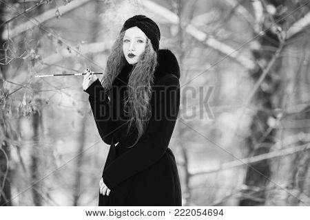 Black and white art monochrome photography. Black and white creative photography. Black and white conceptual image. Beautiful black and white background. Black and white portrait. A woman with long hair in a black coat