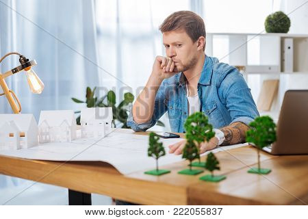 Serious consideration. Smart experienced skilled engineer looking thoughtful while sitting at the table in his comfortable office and staring at the miniature trees