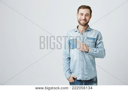 Attractive good-looking male smiling broadly at camera and pointing index finger away, showing something interesting and exciting on studio wall with copy space for your text or advertising content