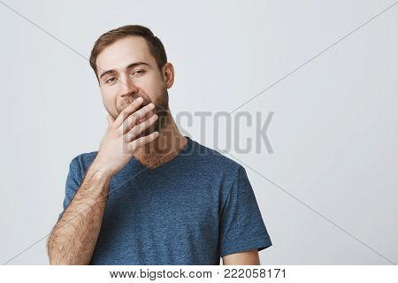 Sleepy muscular guy with dark hair and beard is tired work, yawning, opening widely his mouth, hiding his opened mouth behind his hand. Bored and annoyed european male model