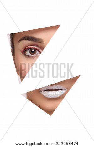 Eye and lips in hole in paper. Beautiful young attractive woman with glamour makeup. Silver lipstick and red arrow. Geometrical figures, triangles