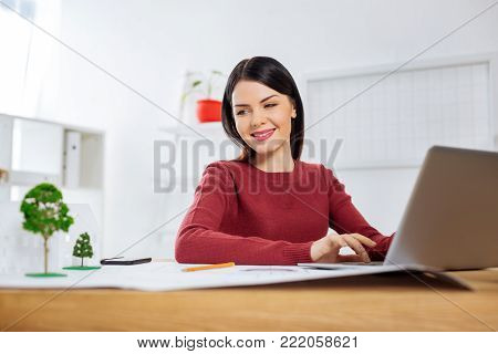 Favorite job. Beautiful young skilled engineer sitting with her hands on the keyboard of a modern laptop and smiling while looking at the miniature trees by her side