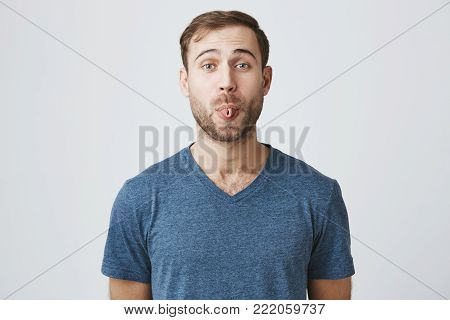 Gloomy young male with beard showing his digust and distaste having gloomy expression demonstrating tongue refusing to do something. Making faces handsome man with rejecting guilt isolated on gray