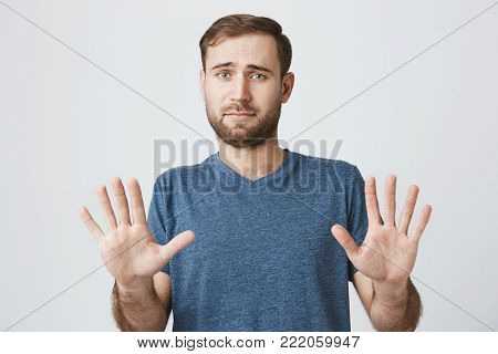 Body language. Disgusted stressed out angry bearded man in blue t-shirt posing against studio wall, keeping hands in stop gesture, trying to defend himself as if saying: Stay away from me