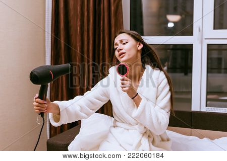 a funny young girl in a white robe dries her long hair with a hair dryer, sings in a comb