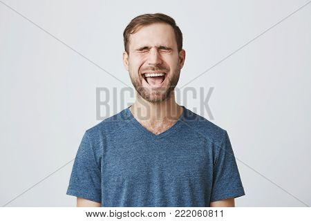 Negative emotions, stress headache and frustration. Stressed frustrated caucasian male with stubble dressed in blue t-shirt closing eyes because of noise, screaming in anger.