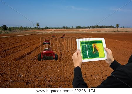 iot smart industry robot 4.0 agriculture concept,industrial agronomist,farmer using tablet to monitor, control automation robotic for row seeding, spraying,weeding or increase more efficiency