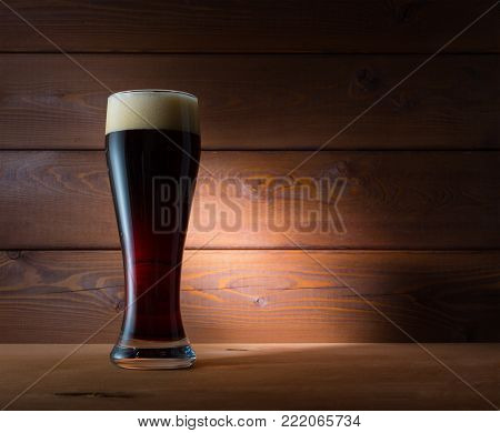 Glass of dark beer on wooden background