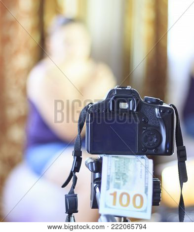 a camera, under it 100 dollars, in focus. in the background the girl does not focus. The concept of earning in a photo.