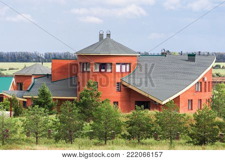 exterior of a large vintage red brick house among trees and fields