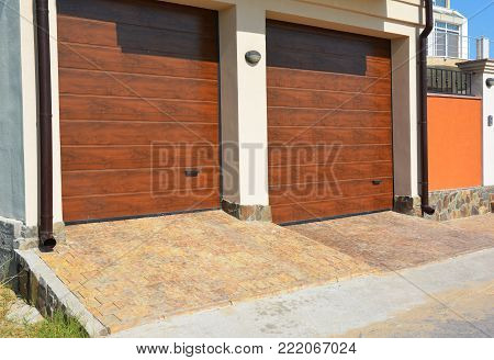 Garage door for two cars with pathway pavement and plastic gutter pipes. Replacing and Repair Garage Door Panels.