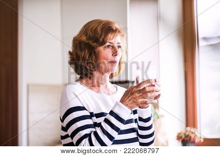 Senior woman in the kitchen. An old woman inside the house, holding a glass of water.