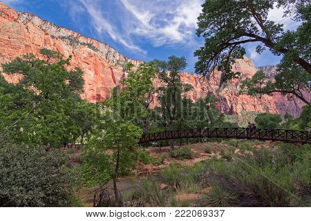 Springdale, Utah, USA - June 3, 2015: A group of tourists, at sunset, cross the bridge over the Virgin-River. In the background the wonderful rock formations of the canyon. Zion Park, Utah.