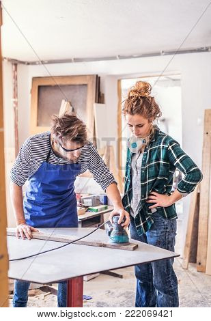 Small business of a young couple. Man and woman worker with a sander in the carpenter workroom.