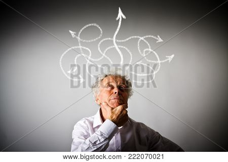 Hesitation. Old man in thoughts and arrows. Old man in white is solving a problem.